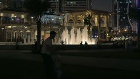 Ο πατέρας και η κόρη παίζουν στα πλαίσια της πόλης νύχτας με μια όμορφη άποψη της πηγής φιλμ μικρού μήκους