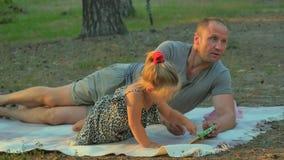 Ο πατέρας και η κόρη περιμένουν μια μητέρα με το καλάθι και τα τρόφιμα στο πικ-νίκ στο δάσος απόθεμα βίντεο