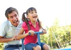 Ο πατέρας και η κόρη που οδηγούν βλέπουν το πριόνι στην παιδική χαρά