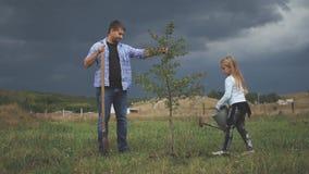 Ο πατέρας και η κόρη φυτεύουν ένα σπορόφυτο δέντρων ο κήπος κορών εκφραστικός γιος προσώπων ανθρώπων προγόνων χρωμάτων mum οικογε φιλμ μικρού μήκους