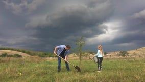Ο πατέρας και η κόρη φυτεύουν ένα σπορόφυτο δέντρων ο κήπος κορών εκφραστικός γιος προσώπων ανθρώπων προγόνων χρωμάτων mum οικογε απόθεμα βίντεο