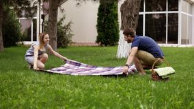 Ο πατέρας και η μητέρα προετοιμάζουν την κάλυψη πικ-νίκ, βάζοντας την στη χλόη χορτοτάπητας δέντρο πεδίων Το μικρό παιδί τρέχει ε απόθεμα βίντεο
