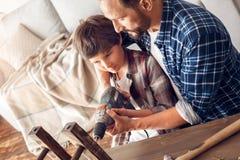 Ο πατέρας και λίγος γιος που στέκονται στο σπίτι το τρυπάνι εκμετάλλευσης μπαμπάδων μαζί με την τρυπώντας με τρυπάνι καρέκλα αγορ στοκ εικόνα με δικαίωμα ελεύθερης χρήσης