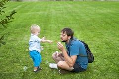 Ο πατέρας και ο γιος φυσούν ένα σαπούνι βράζουν Στοκ Εικόνα