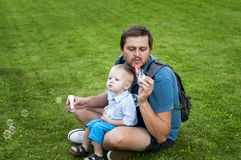 Ο πατέρας και ο γιος φυσούν ένα σαπούνι βράζουν Στοκ Φωτογραφία