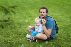 Ο πατέρας και ο γιος φυσούν ένα σαπούνι βράζουν Στοκ φωτογραφία με δικαίωμα ελεύθερης χρήσης