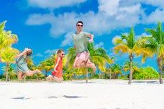 Ο πατέρας και τα μικρά κορίτσια έχουν πολλή διασκέδαση στην άσπρη αμμώδη παραλία Στοκ εικόνες με δικαίωμα ελεύθερης χρήσης
