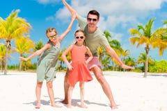 Ο πατέρας και τα μικρά κορίτσια έχουν πολλή διασκέδαση στην άσπρη αμμώδη παραλία Στοκ φωτογραφία με δικαίωμα ελεύθερης χρήσης