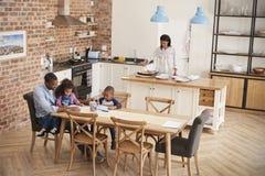 Ο πατέρας και τα παιδιά που σύρουν στον πίνακα ως μητέρα προετοιμάζουν το γεύμα Στοκ φωτογραφίες με δικαίωμα ελεύθερης χρήσης