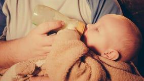 Ο πατέρας κρατά το μικρό παιδί διαθέσιμο και τις τροφές με το γάλα από ένα μπουκάλι απόθεμα βίντεο