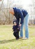 Ο πατέρας μαθαίνει το γιο του για να πηγαίνει υπαίθρια την άνοιξη Στοκ Εικόνες