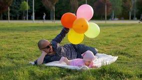 Ο πατέρας με τα μπαλόνια βρίσκεται στο άσπρο κάλυμμα και η κόρη του βρίσκεται κοντά σε τον και μαδά την πράσινη χλόη στο πάρκο πό απόθεμα βίντεο
