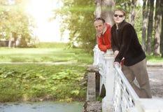 Ο πατέρας με τον ενήλικο γιο στο πάρκο στη γέφυρα στοκ εικόνα