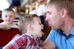 Ο πατέρας με το γιο παρουσιάζει γλώσσες τους στοκ εικόνες