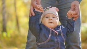 Ο πατέρας οδηγεί τα χέρια ενός μικρού παιδιού στο πάρκο φθινοπώρου o φιλμ μικρού μήκους