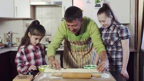 Ο πατέρας παρουσιάζει δύο κόρες του πώς να ξεδιπλώσει τη ζύμη Μια από τις κόρες έχει κάτω από το σύνδρομο απόθεμα βίντεο