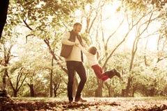 Ο πατέρας στο πάρκο με τα χέρια εκμετάλλευσης κορών και περιστρέφεται μέσα στοκ εικόνα