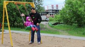 Ο πατέρας ταλαντεύεται λίγο όμορφο κορίτσι στην ταλάντευση στην παιδική χαρά απόθεμα βίντεο