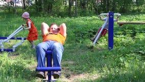 Ο πατέρας, το αγόρι και το μικρό κορίτσι κάνουν τις ασκήσεις στους υπαίθριους γυμναζομένους στο πράσινο πάρκο απόθεμα βίντεο