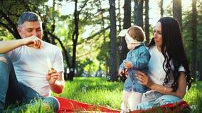 Ο πατέρας φυσά τις φυσαλίδες σαπουνιών για την κόρη μικρών παιδιών του και η μητέρα κρατά το κορίτσι απόθεμα βίντεο