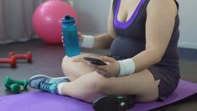 Ο παχύς να τυλίξει γυναικών αθλητισμός app στο smartphone της, απώλεια βάρους προσοχής οδηγεί απόθεμα βίντεο