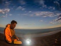 Ο πεζοπορία τουρίστας έχει ένα υπόλοιπο στο στρατόπεδό του τη νύχτα κοντά στην πυρά προσκόπων στοκ εικόνες