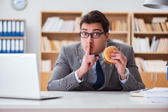 Ο πεινασμένος αστείος επιχειρηματίας που τρώει το σάντουιτς άχρηστου φαγητού Στοκ Εικόνα