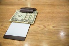 Ο πελάτης έδωσε τα μετρητά σε χαρτί λογαριασμών Άκρες τραπεζογραμματίων αμερικανικών δολαρίων στη μαύρη παραλαβή λογαριασμών δέρμ Στοκ Εικόνα