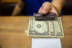 Ο πελάτης έδωσε τα μετρητά σε χαρτί λογαριασμών Άκρες τραπεζογραμματίων αμερικανικών δολαρίων στη μαύρη παραλαβή λογαριασμών δέρμ Στοκ φωτογραφία με δικαίωμα ελεύθερης χρήσης
