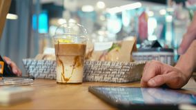 Ο πελάτης αγοράζει το take-$l*away πάγο Latte και πληρώνει από την πιστωτική κάρτα σε ένα κατάστημα καφέδων απόθεμα βίντεο