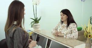 Ο πελάτης γραφείων υποδοχής έχει μια συνομιλία με τη βοήθεια 4K απόθεμα βίντεο