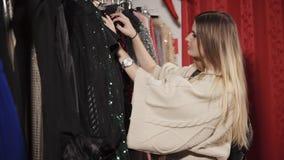 Ο πελάτης γυναικών επιλέγει ένα λαμπρό φόρεμα στην εμπορική αίθουσα απόθεμα βίντεο