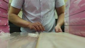 Ο πελάτης ελέγχει την ποιότητα του φυλλόμορφου δαπέδου στο κατάστημα υλικού απόθεμα βίντεο