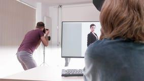 Ο πελάτης που εξετάζει τις φωτογραφίες ο φωτογράφος παίρνει απόθεμα βίντεο