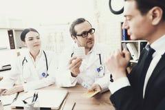Ο πεπειραμένος γιατρός ορίζει στον ασθενή για τη δόση των ταμπλετών στο ιατρικό γραφείο Στοκ Φωτογραφίες