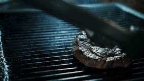 Ο πεπειραμένος μάγειρας τηγανίζει τη φέτα βόειου κρέατος στη σχάρα στην κουζίνα του εστιατορίου απόθεμα βίντεο
