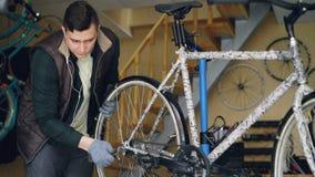Ο πεπειραμένος μηχανικός συγκεντρώνει το ποδήλατο ρυθμίζοντας την πίσω ρόδα κατά τη διάρκεια της συντήρησης του οχήματος στον εργ απόθεμα βίντεο