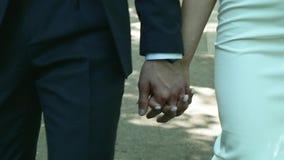 Ο περίπατος παντρεμένων ζευγαριών κινηματογραφήσεων σε πρώτο πλάνο πρόσφατα που κρατά μαζί παραδίδει το πάρκο πόλεων απόθεμα βίντεο