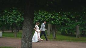 Ο περίπατος Newlyweds στον κήπο και έχει τη διασκέδαση φιλμ μικρού μήκους