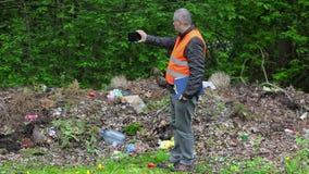 Ο περιβαλλοντικός ανώτερος υπάλληλος παίρνει τις εικόνες στο έξυπνο τηλέφωνο στο μολυσμένο πάρκο απόθεμα βίντεο