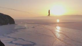 Ο περιπατητής σχοινιών σχοινοβασίας ισορροπεί σε ένα σχοινί μεταξύ δύο βράχων επάνω από μια παγωμένη λίμνη απόθεμα βίντεο