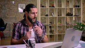 Ο περιστασιακός αστείος καυκάσιος τύπος με τη μακρυμάλλη και μαύρη γενειάδα χορεύει καθμένος στον υπολογιστή γραφείου στο lap-top απόθεμα βίντεο