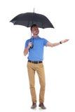 Ο περιστασιακός νεαρός άνδρας αισθάνεται τη βροχή με ένα χέρι Στοκ φωτογραφία με δικαίωμα ελεύθερης χρήσης