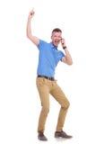 Ο περιστασιακός νεαρός άνδρας δείχνει επάνω ενώ στο τηλέφωνο Στοκ εικόνα με δικαίωμα ελεύθερης χρήσης