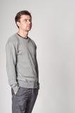 Ο περιστασιακός νεαρός άνδρας με την ελαφριά γενειάδα, παραδίδει τις τσέπες, κοιτάζοντας έξω Στοκ Εικόνα