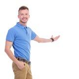 Ο περιστασιακός νεαρός άνδρας παρουσιάζει κάτι Στοκ φωτογραφία με δικαίωμα ελεύθερης χρήσης