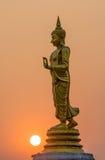 Ο περπατώντας Βούδας και το ηλιοβασίλεμα Στοκ Εικόνα
