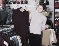 Ο πελάτης νέων κοριτσιών αποφασίζει σχετικά με το θερμό πουλόβερ Στοκ Εικόνα