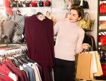 Ο πελάτης νέων κοριτσιών αποφασίζει σχετικά με το θερμό πουλόβερ Στοκ Εικόνες