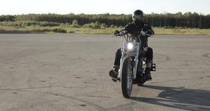 Ο ποδηλάτης νεαρών άνδρων οδηγά μια μοτοσικλέτα στο κράνος στο δρόμο, μπροστινή άποψη απόθεμα βίντεο